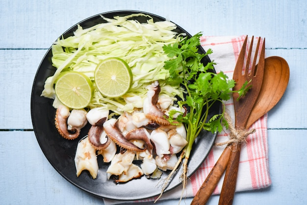 Grilled squid salad with lime herbs and spices on dining table, tentacles octopus cooked appetizer food hot and spicy seafood cooked