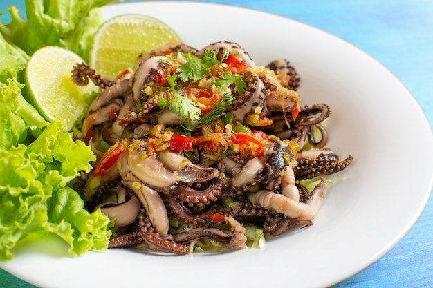 Grilled squid topped with seafood sauce on a white plate with  lettuce and lemon decoration placed on a blue wooden table.
