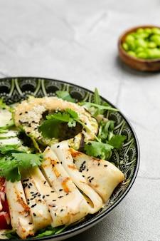 아바카도 샐러드를 곁들인 구운 오징어와 복사 공간이 있는 신선한 야채 클로즈업