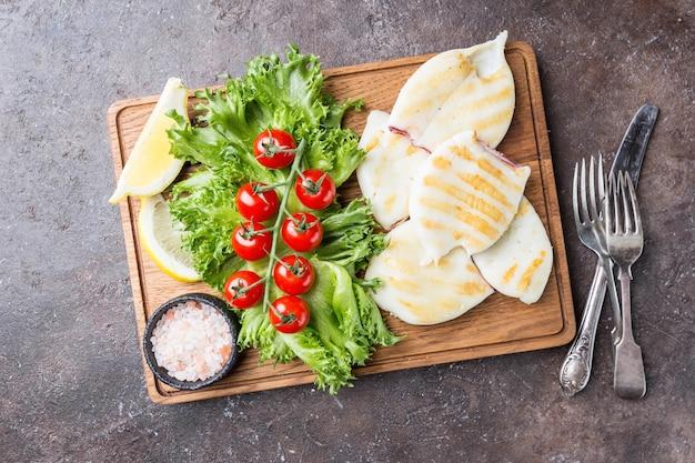 暗闇の上の木製まな板の上にレモンと野菜とイカのグリル