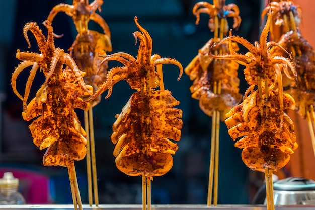 Grilled squid with mala chilli on a stick at muslim street food, china
