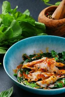 어두운 테이블에 시금치와 소스를 곁들인 구운 오징어. 식사 근접 촬영의 성분