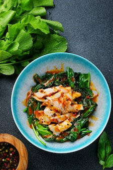 어두운 테이블에 시금치와 소스를 곁들인 구운 오징어. 식사 평면도의 성분