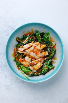 Grilled squid with spinach top view