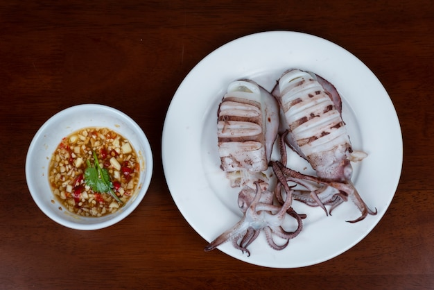 Grilled squid with thai seafood dipping sauce on white plate on wood table