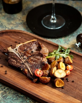 Grilled stake with black pepper baked potato tomatoes and rosemary on board