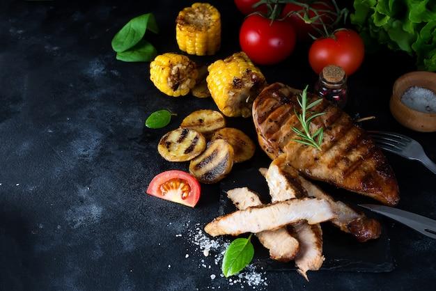 Жареный стейк и овощ, печеный картофель и зеленый салат на темном