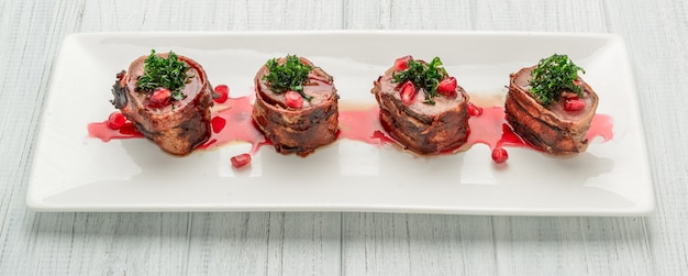Grilled steak filet mignon wrapped bacon on a white plate