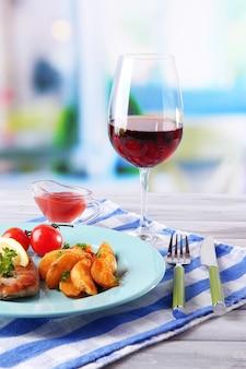 밝은 배경에 테이블에 구운 스테이크, 구운 야채와 튀긴 감자 조각