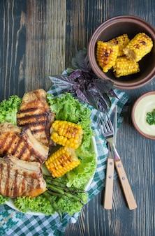 暗い背景の木にスパイス、ハーブ、野菜と丸いボウルのグリルステーキ。肉料理。暗い背景の木。コピースペース。