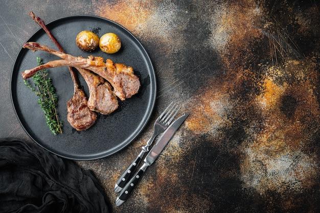 구운 양고기 고기 스테이크, 야채, 기름 및 종 세트, 접시에, 오래 된 어두운 소박한 테이블, 평면도 평면 누워 슬라이스에 잘라