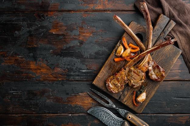 오래 된 어두운 나무 테이블, 평면도 평면 누워 나무 서빙 보드에 야채, 기름, 종 세트와 조각에 잘라 양고기 고기 구이 스테이크