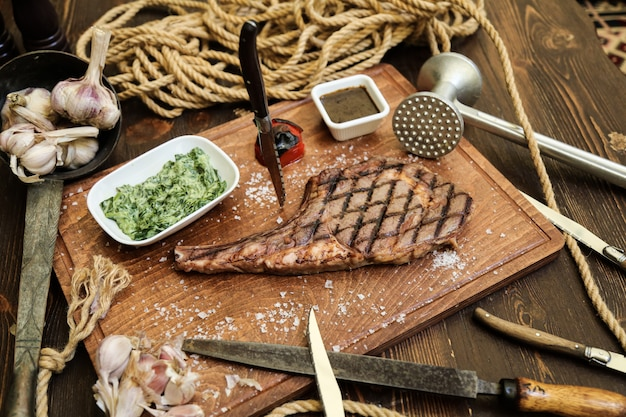 나무 boardsalt 마늘 토마토 향신료 측면보기에 구운 스테이크
