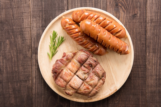 Grilled steak and sausage on a wooden background