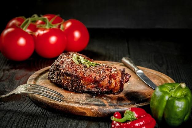 향신료와 신선한 허브로 맛을 낸 그릴 스테이크를 신선한 토마토와 신선한 허브를 곁들인 나무 판자에 제공합니다.