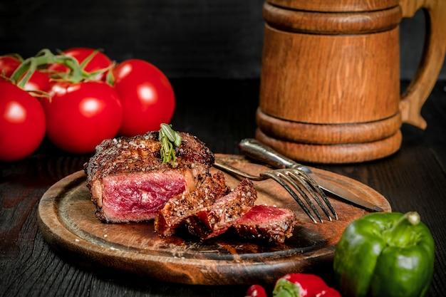 향신료와 신선한 허브로 맛을 낸 구운 스테이크는 나무 판자에 맥주 한 잔, 신선한 토마토, 빨강 및 피망과 함께 제공됩니다. 검은 나무 배경. 정물