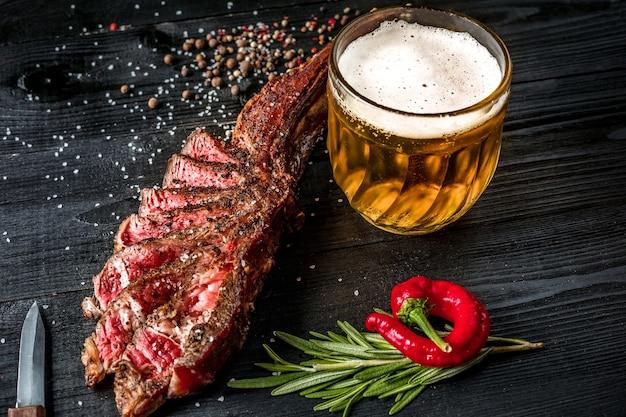 향신료와 신선한 허브로 맛을 낸 구운 스테이크에 맥주 한 잔, 신선한 고추와 함께 제공됩니다. 검은 나무 배경. 정물