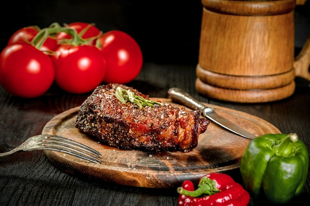 Grilled steak seasoned with spices and fresh herbs served on a wooden board with wooden mug of beer ...