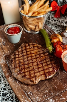 Grilled steak served with french fries ketchup and grilled vegetables