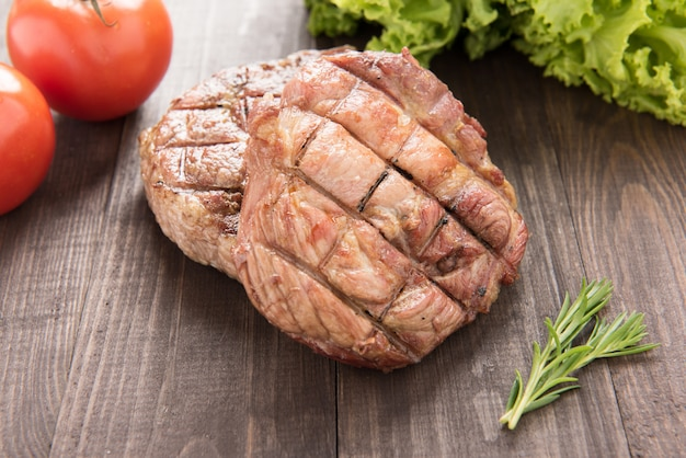 Grilled steak and vegetables on a wooden background