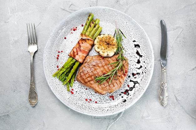 Жареный стейк со спаржей и листом розмарина в тарелке сверху на конкретном фоне с копией пространства.
