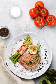 Стейк на гриле со спаржей, листом розмарина и жареным чесноком на тарелке и ингредиентами с овощами на бетонном столе