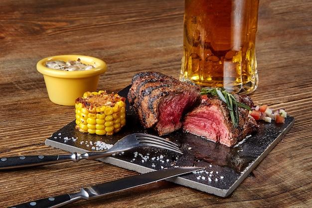 도마에 버섯 소스와 함께 옥수수를 곁들인 구운 스테이크와 나무 테이블에 맥주 한 잔