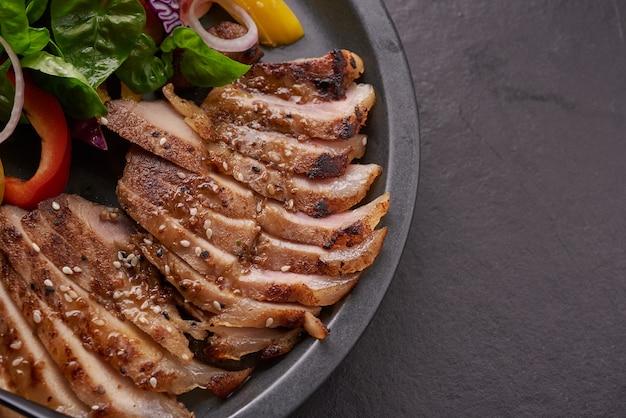 新鮮な野菜、ピーマン、トマト、赤玉ねぎ、ピンクペッパー、スパイスを使ったグリルステーキ。自家製のおいしい料理。美味しくて健康的な食事のコンセプト。黒い石の表面。ポークステーキとサラダ