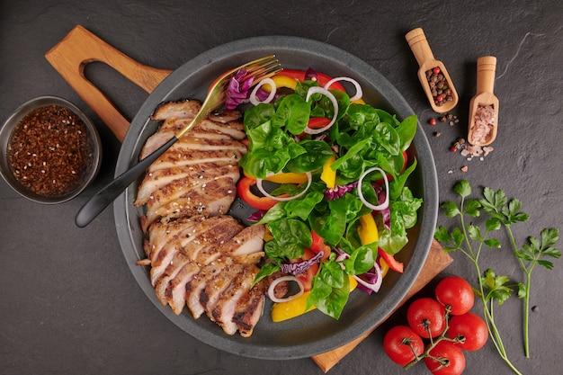 新鮮な野菜、ピーマン、トマト、赤玉ねぎ、ピンクペッパー、スパイスを使ったグリルステーキ。自家製のおいしい料理。美味しくて健康的な食事のコンセプト。黒い石の表面。ポークステーキとサラダ 無料写真