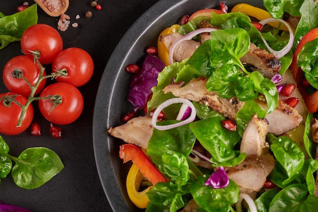 Grilled steak with fresh vegetable, sweet pepper, tomatoes, red onion, pink pepper and spices. home made tasty food. concept for tasty and healthy meal. black stone surface. pork steak with salad