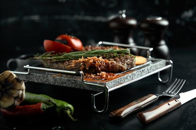 Стейк на гриле с ножом и вилкой, вырезанные на черном каменном сланце. стейк на горячем мраморном камне.