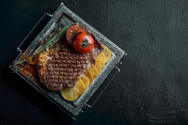 Стейк на гриле с ножом и вырезанной на черном каменном сланце. стейк на горячем мраморном камне. copyspace, темный, еда моды.