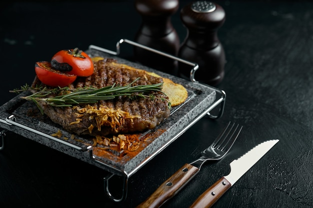 Grilled steak with knife and k carved on black stone slate. steak on a hot marble stone. copyspace, dark , food fashion .