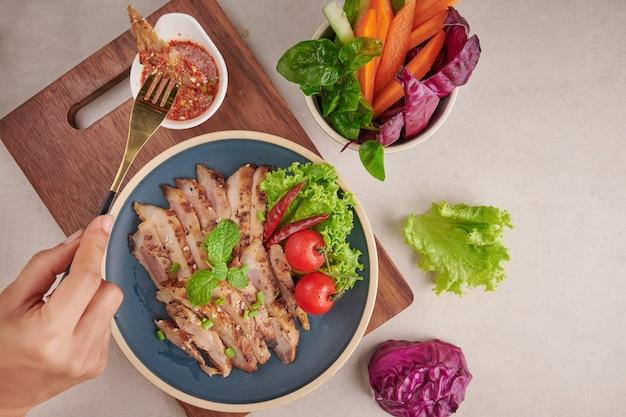野菜とスパイスを混ぜたグリルステーキ。自家製のおいしい料理。石の表面。ポークステーキとサラダ。豚肉のグリルは、最も人気のあるタイ料理の1つです。豚肉のスパイシーディップ焼き。