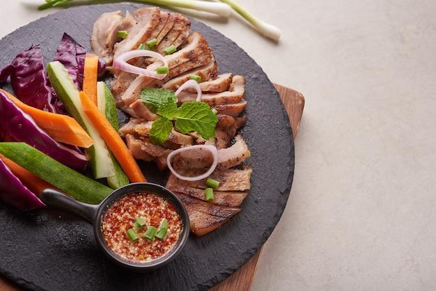 Bistecca alla griglia con verdure miste e spezie. cibo gustoso fatto in casa. superficie di pietra. bistecca di maiale con insalata. il maiale alla griglia è uno dei piatti thailandesi più popolari. maiale alla griglia con salsa piccante.