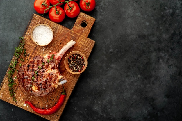 Grilled steak with spices, thyme on a stone background. with copy space for your text