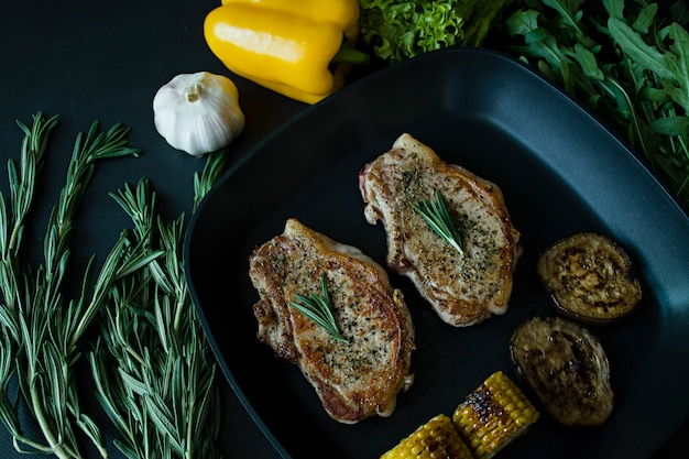 Grilled steak with vegetables in a pan decorated with rosemary.