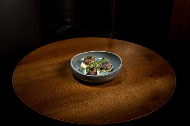 Стейк на гриле с овощами пюре на плите на деревянном столе.