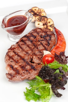 Grilled steak with vegetables and sauce on white background