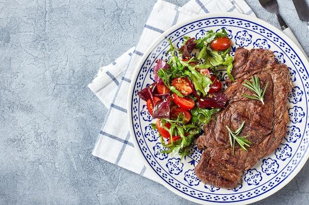 グリルステーキと野菜サラダ。テーブルセッティング、フードコンセプト。上面図