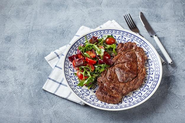 구운 스테이크와 야채 샐러드. 테이블 설정, 음식 개념.