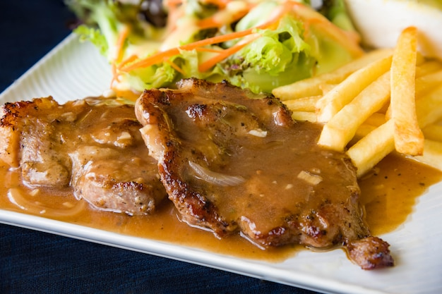 Grilled steaks, boiled french fries and vegetable salad