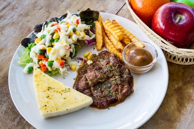 Стейки на гриле в белом блюде на старом деревянном столе, печеный картофель и овощной салат