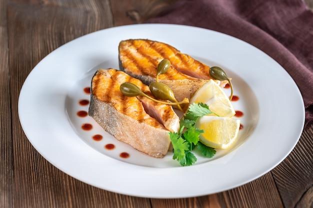 Жареные стейки арктического голца на белой тарелке