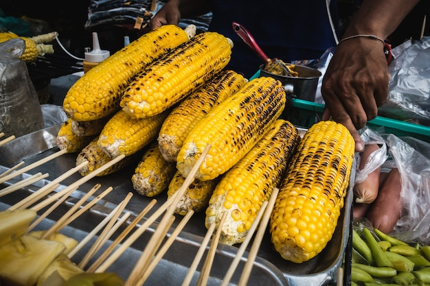 Grilled sweet corn on sticks