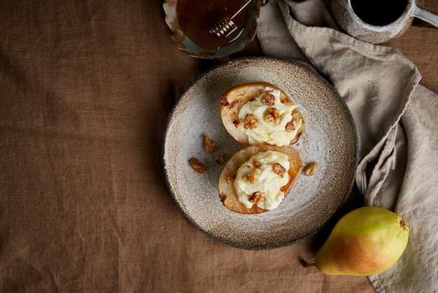 Жареные сладкие груши с орехами и медом на коричневой скатерти осенний десерт