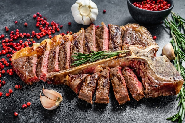 Grilled t-bone steak. cooked tbone beef. black background. top view.