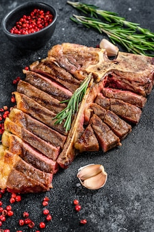 Жареный стейк на косточке. приготовленная говядина. черное пространство. вид сверху