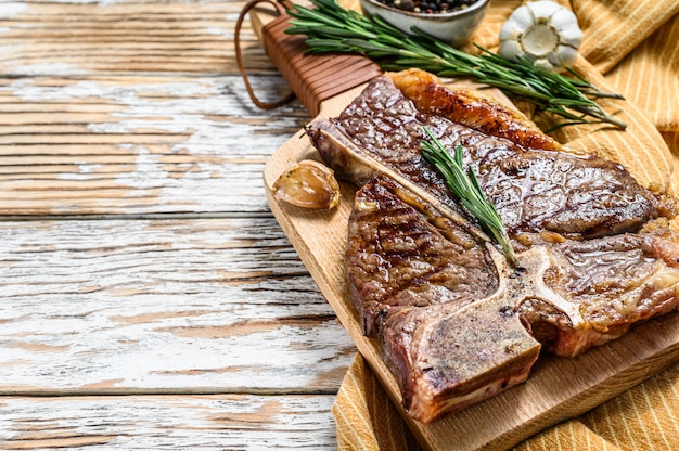 Жареный стейк на косточке на разделочной доске. приготовленная говядина. белое деревянное пространство. вид сверху. копировать пространство