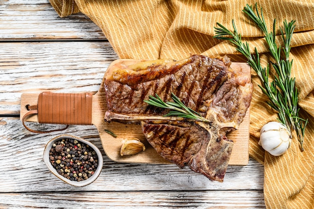 Жареный стейк на косточке на разделочной доске. приготовленная говядина. белое деревянное пространство. вид сверху
